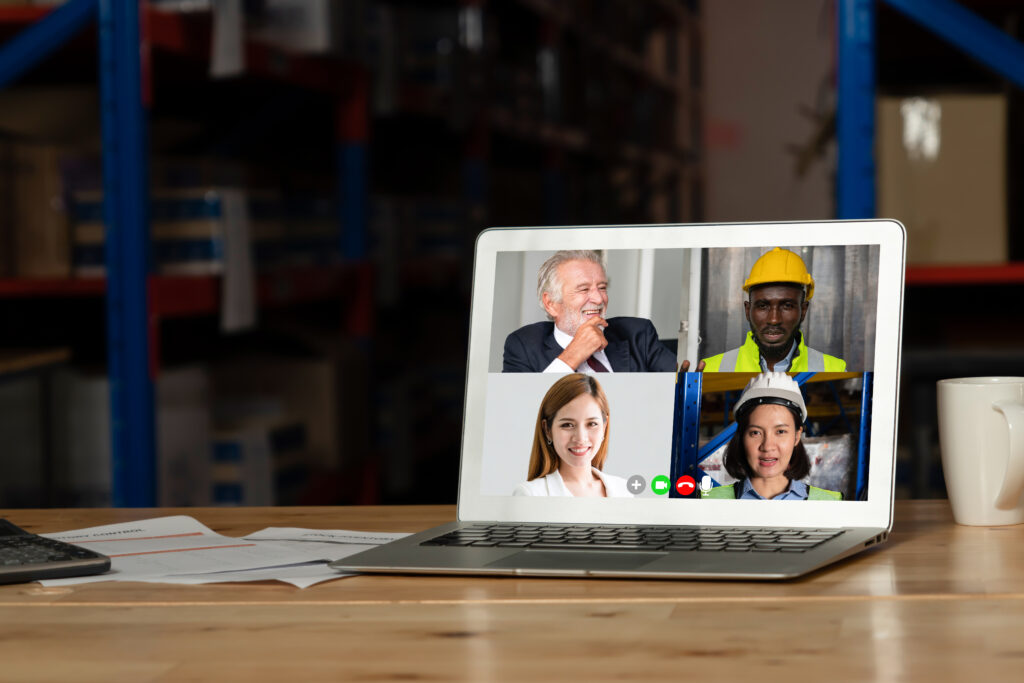 Warehouse staff talking on video call at computer screen in storage warehouse . Online software technology connects people working in logistic factory by virtual conference call on internet network .