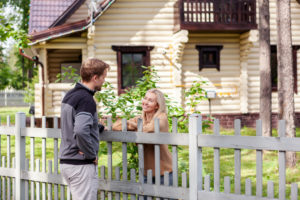 Man and women cheerfully talking over fence